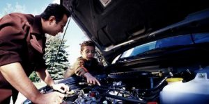 Father and son repair a car