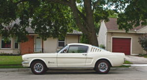 White Vintage Ford Mustang parked on residential street