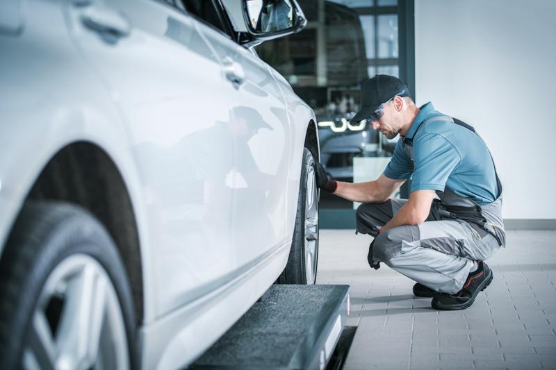 Young man polishing car in service